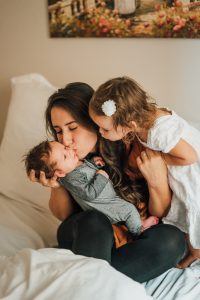 mom kissing a baby while a toddler looks over her shoulder, busyness with kids keeps moms from having social lives